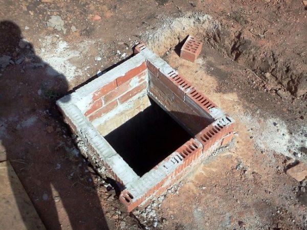 Фото небольшой ямы, обложенной кирпичом