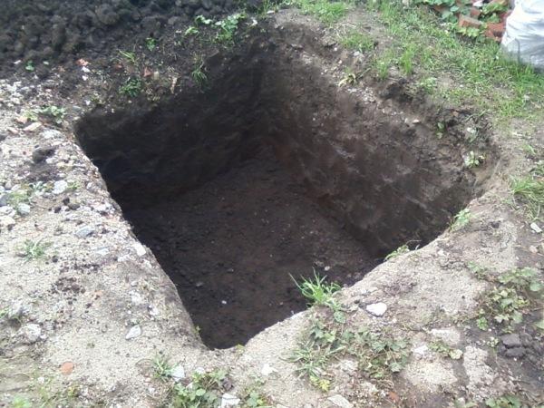 После выкапывания ямы ее стенки лучше укрепить с помощью досок