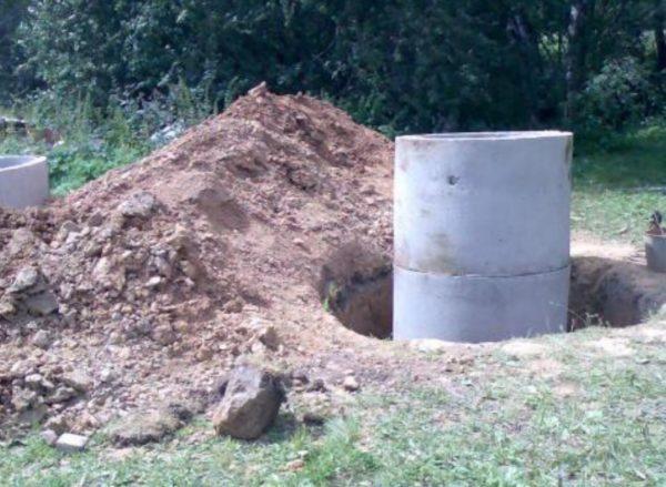 Процесс сооружения колодца из бетонных колец.