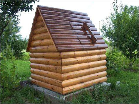 Домик и колодец внутри. Комбинация металла (крыша из профнастила) и дерева (стены из оцилиндрованного бревна)