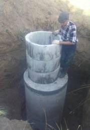 Фотография монтажа колодца из бетонных изделий, показывающая объем данных элементов, из которого можно получить представление и о весе