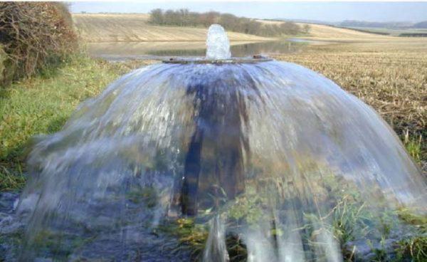 Из известнякового водоносного горизонта вода выбрасывается на поверхность под давлением