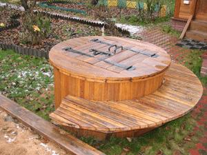 Можно пойти еще дальше и не только обшить колодезное кольцо деревом, а сделать по окружности декоративную скамью.