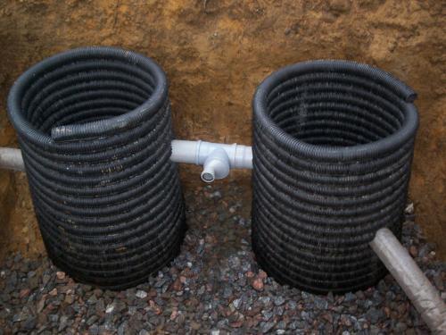 На дне ямы уложенный гравий для фильтрационного колодца.