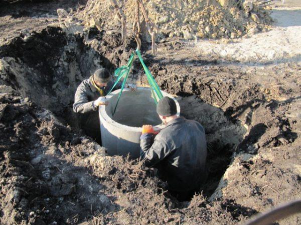 На фото – строительство бетонного колодца-гасителя