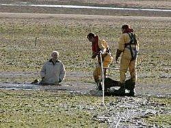 На фото изображены спасатели, прибывшие на помощь человеку, который увяз в плывуне.