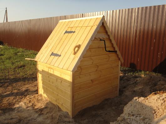 На фото: полная обшивка колодца и вправду делает конструкцию похожей на домик