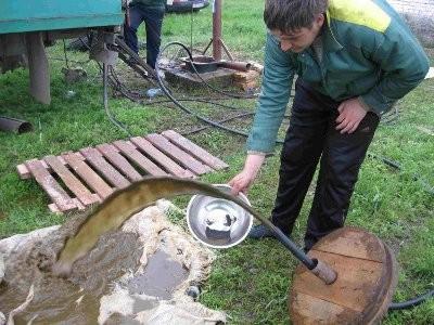 На фото видно, что из скважины при очистке поднимается заиленная вода.