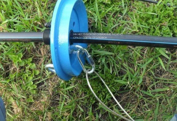 Оголовок скважины с напорной трубой и закрепленным верхним концом троса.