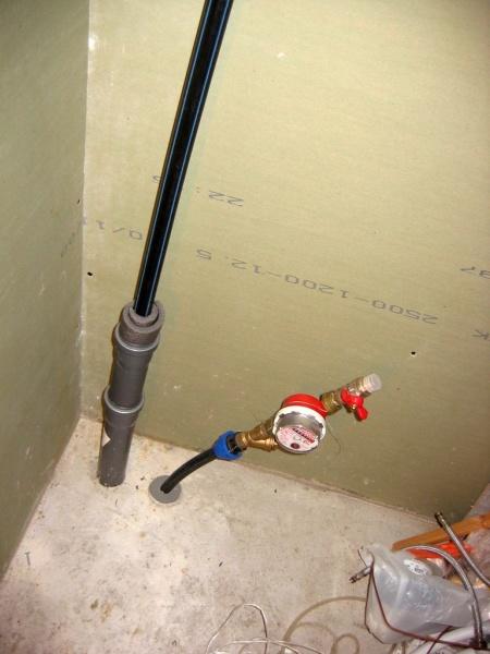 Толстый слой утеплителя и канализационная труба служат надежной защитой для ввода воды в дом