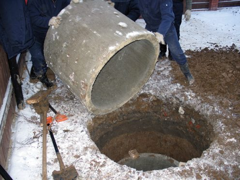В готовый котлован опускаются кольца из бетона.